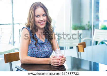 Pretty brunette having a smoothie in a coffee shop