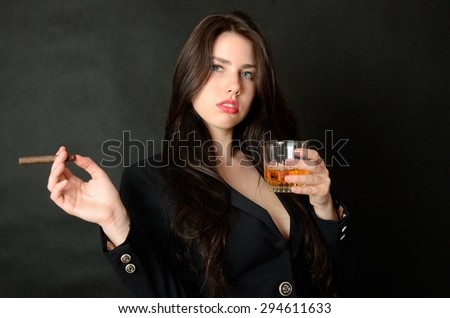 Pretty brunette model holding glass of whisky and cigar. Girl with confident face expression, wearing dark tail-coat.