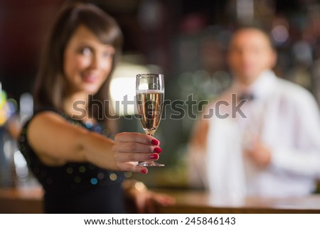 Pretty brunette smiling at camera with champagne in a bar
