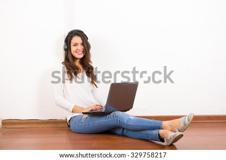 Pretty brunette wearing denim jeans and white top sitting on wooden surface her back against wall, black headphones listening to music using laptop.