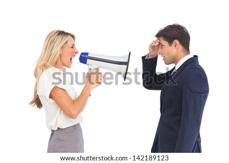 Pretty businesswoman shouting at a businessman with megaphone