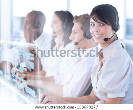 Pretty call center worker using futuristic holographic interface smiling at camera in office