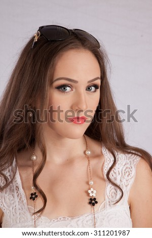 Pretty Caucasian girl looking thoughtful with sunglasses on the top of her head