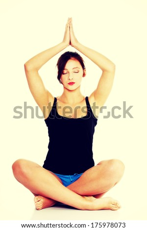 Pretty caucasian teen girl sitting on the floor and practising yoga.