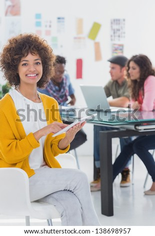 Pretty editor holding tablet with team working behind her