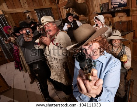 Pretty elderly lady with pistol in old saloon