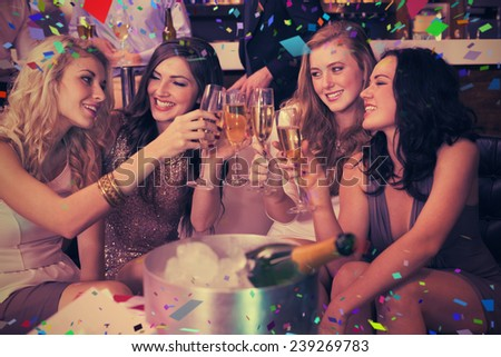 Pretty friends drinking champagne together against flying colours