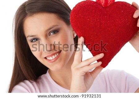 Pretty girl holding red heart at valentine's day smiling.?