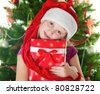Pretty Girl in Santa hat with gift against the background of the Christmas Tree - stock photo