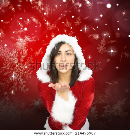 Pretty girl in santa outfit blowing against red snow flake pattern design