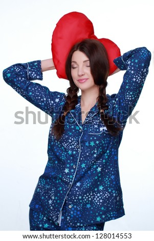 Pretty girl keeps a red pillow in blue pajamas in the form of heart on Holiday theme