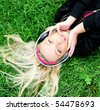 Pretty girl lying on grass and listening music - stock photo