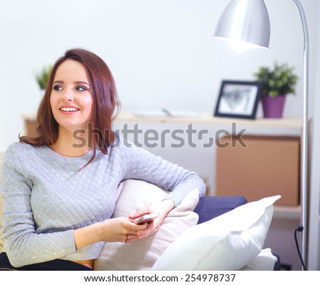 Pretty girl using her smartphone on  couch at home in the living room