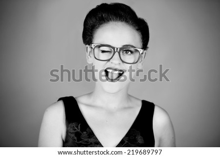 Pretty girl winking while wearing big red glasses in front of a grey background in black and white