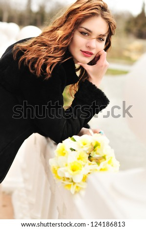 pretty girl with daffodils in windy spring day