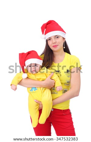 Happy young mother with the cute little baby dressed in new year caps