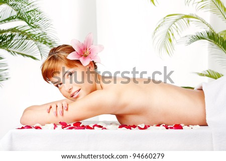 Pretty lady with flower in her hair relaxing on massage table