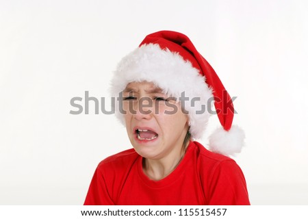 pretty little boy in santa hat crying