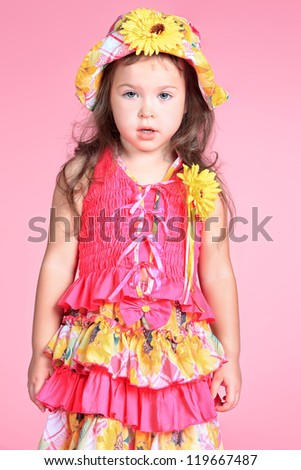 Pretty little girl in a floral hat and dress over pink background.