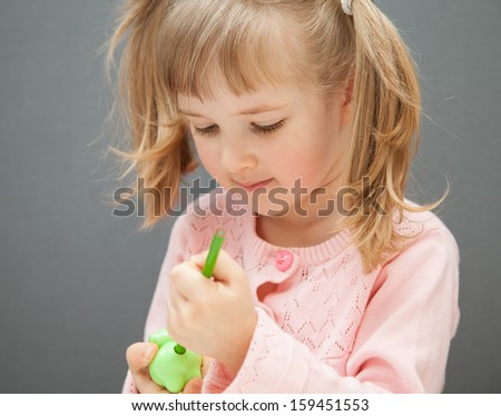 Pretty little girl sharpening a green pencil, grey background