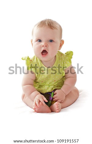Pretty 6 month old baby girl with big blue eyes and ruffled dress sits and vocalizes. She holds a rattle. Pastels, isolated on white background, vertical, copy space.