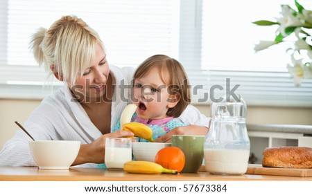Pretty mother and daughter having breakfast in the kitchen