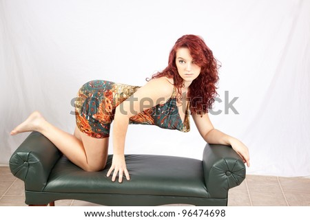 Pretty redhead teenage girl kneeling on a bench and leaning on her elbows, looking wistfully back over her shoulder