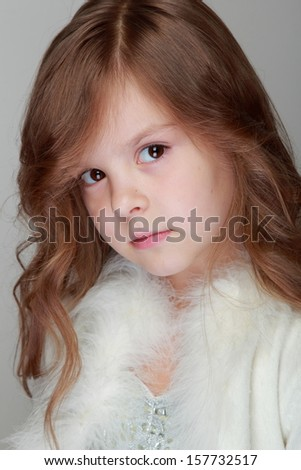 Pretty sad little child with brunette curly long hair on gray background
