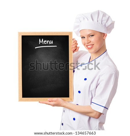 Pretty smiling chef woman holding menu blackboard. Young cheerful female cook/ baker showing empty chalkboard for promotion. Isolated on white background.
