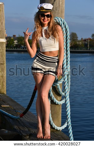 Pretty smiling woman dressed as a sailor posing on the pier.