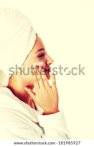 Pretty teen caucasian girl in robe putting creme on her face.