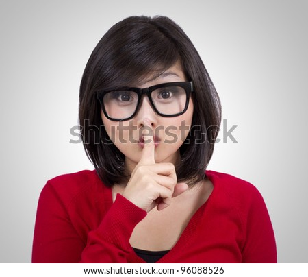 pretty teenage girl wearing nerd glasses making silence sign