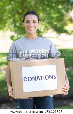 Pretty volunteer holding a donation box in park on a sunny day