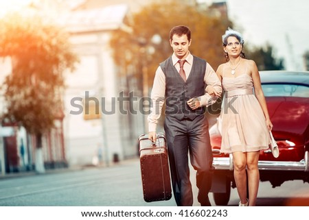 Pretty walking couple with the suitcase on the vintage car background.