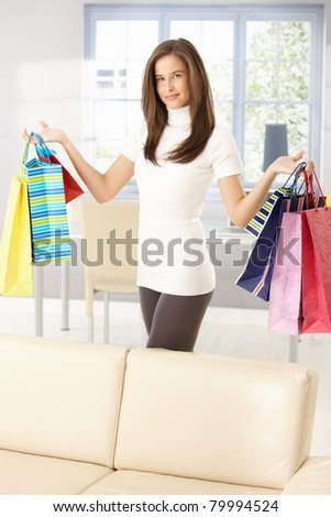 Pretty woman after shopping standing at home, posing holding colorful shopping bags happily.?