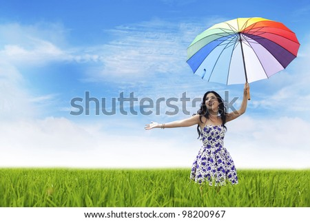 Pretty woman carrying colorful umbrella having fun on a field