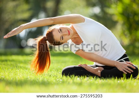 Pretty woman doing yoga exercises in the park