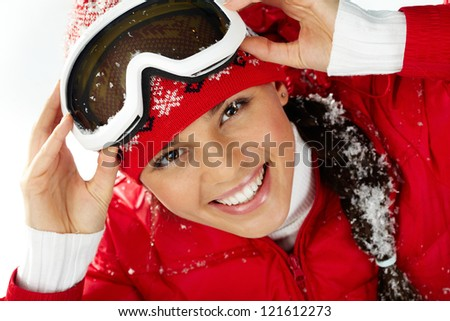 Pretty woman in goggles and winter clothes looking at camera with smile