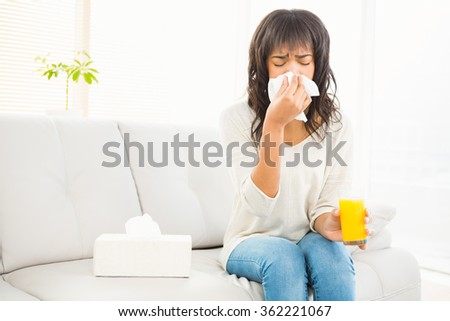 Pretty woman sneezing on couch at home in living room