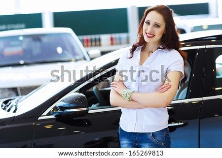 Pretty woman standing near car at car center. Choosing a car