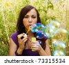 Pretty woman  starts soap bubbles - stock photo