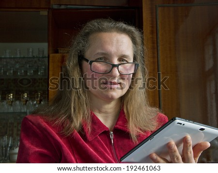 Pretty woman using tablet computer at home.