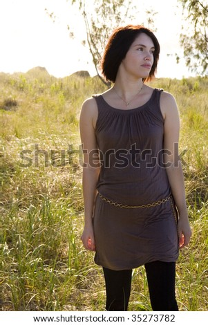 pretty woman walking in the grass at the beach