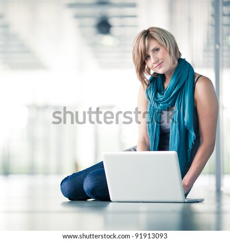 Pretty young female student/businesswoman with a laptop computer at college/university campus/work (shallow DOF; color toned image)