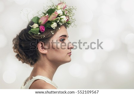 Pretty young girl in a flower wreath of roses in profile