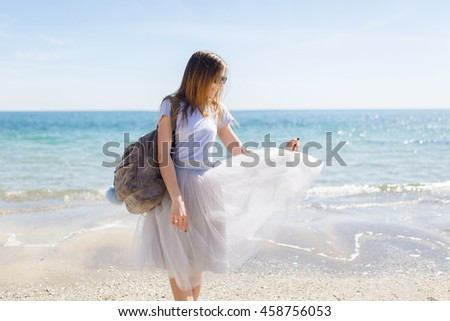 Pretty young girl with bag is standing near sea.  She has long hair and wind playing with her gray lush skirt.