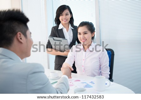 Pretty young lady shaking hands with a male entrepreneur introducing herself or concluding a deal