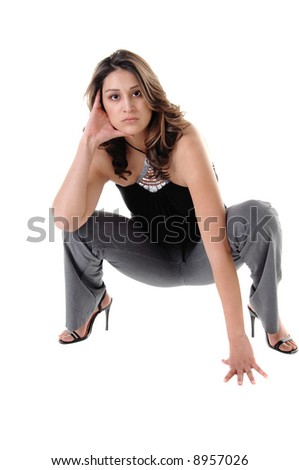 Pretty young Mexican woman squatting on the floor in grey pants, black blouse