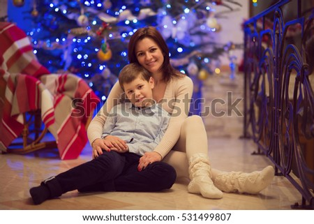 Pretty young mother sitting with her happy son which is in santa hat