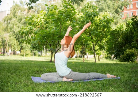 Pretty young red-haired woman wearing white T-shirt and grey pants doing yoga stretching lying on blue mat in the park